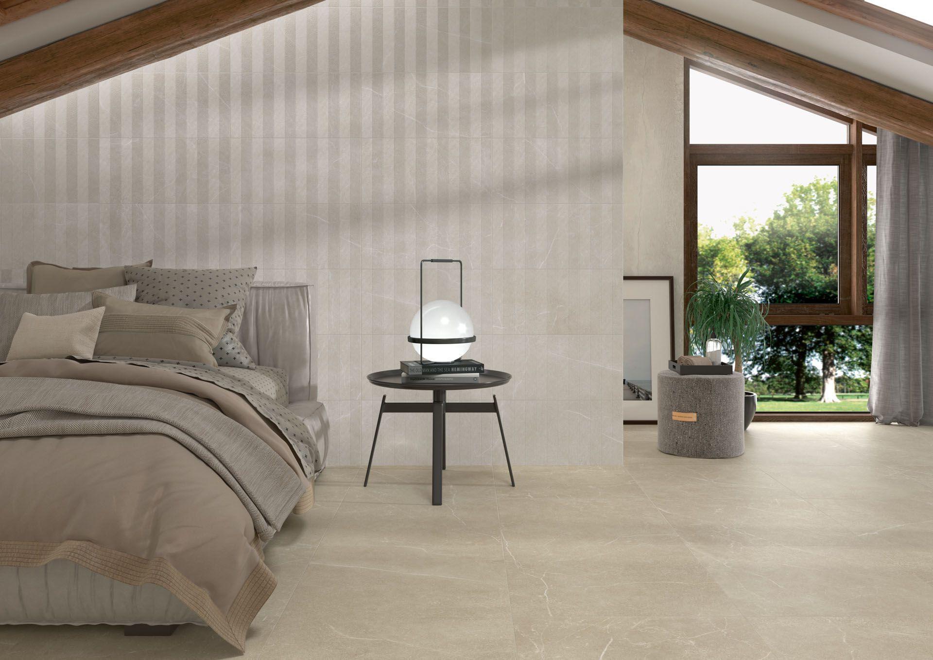 Sypialnia utrzymana w beżu z dużym łóżkiem, okrągłym stoliczkiem z lampą, oknem z szarymi zasłonami, obrazem i płytkami Soapstone White