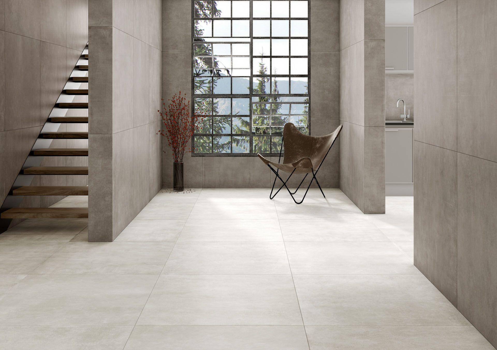 Minimalistyczny przedpokój w szarości z oknem, wejściem do kuchni, schodami, krzesłem i kwiatem oraz płytkami imitującymi beton
