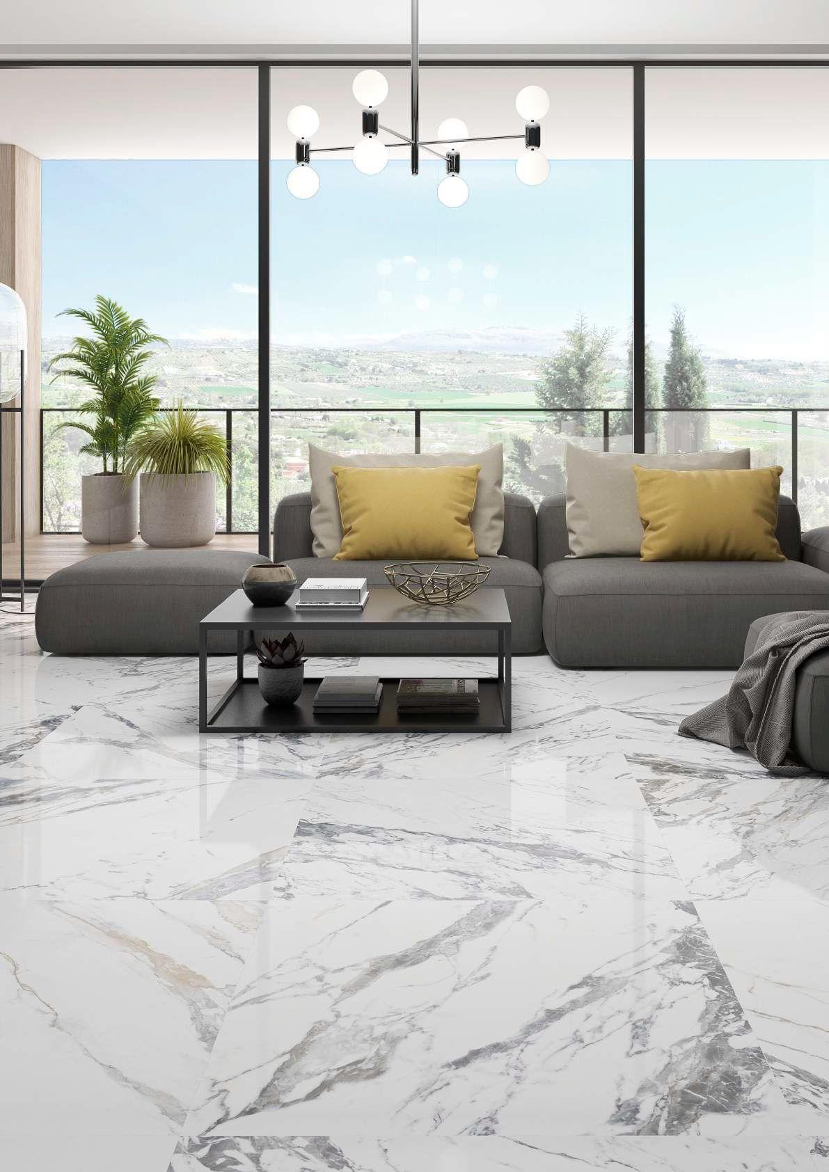 Duży salon z płytkami imitującymi marmur szarą kanapą