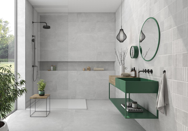Szara łazienka z kabiną prysznicową, szafką wiszącą w kolorze zielonym, okrągłym lustrem, lampą wiszącą, kwiatami i płytkami imitującymi beton