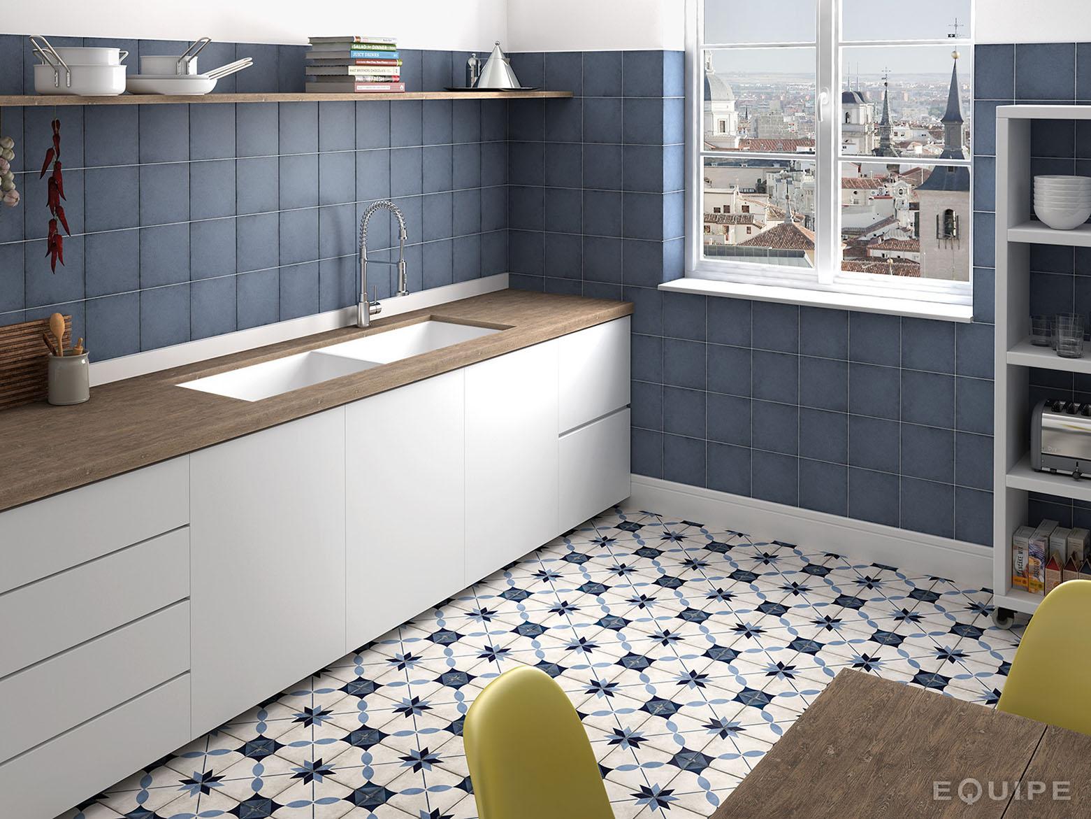 Kuchnia z niebieskimi kafelkami na ścianie, płytkami patchworkowymi Art Nouveau Arcade Blue, białymi meblami z drewnianymi blatami, wiszącą półką z naczyniami, białą szafką, stołem z kolorowymi krzesłami i oknem