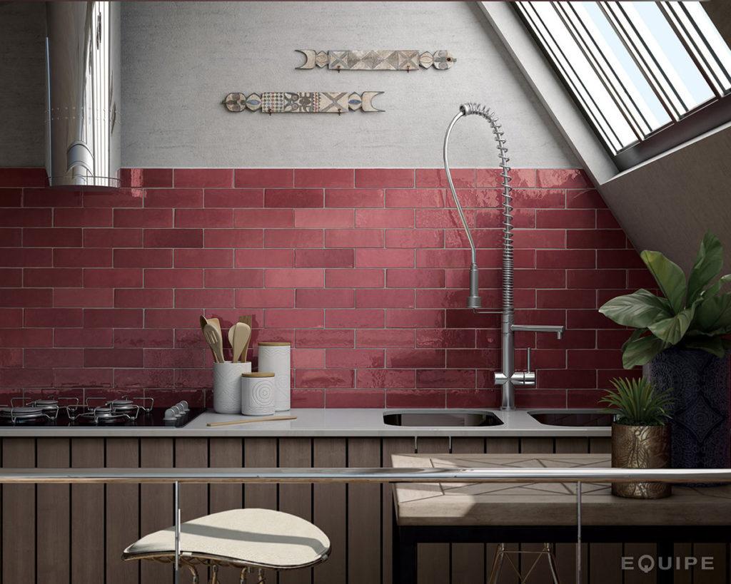 Fragment kuchni z długim blatem, zlewem, wysoką baterią, czarną kuchenką, srebrnym okapem, naczyniami, kwadratowym stołem i krzesłem oraz płytkami Equipe Artisan Burgundy 6,5x20