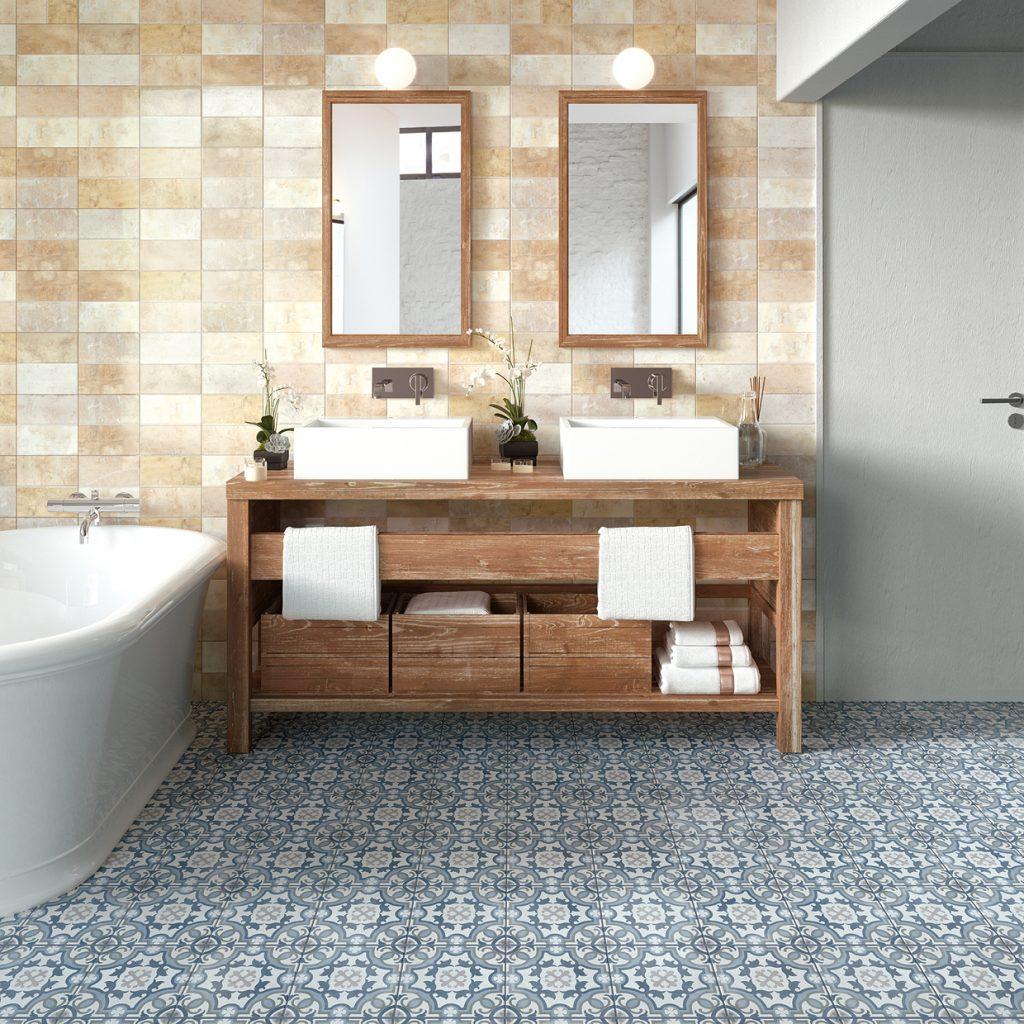 Łazienka ze ścianą wyłożoną beżowymi cegiełkami imitującymi glinę i niebieską podłogą z płytkami patchworkowymi, białą wanną wolnostojącą z baterią wannową ścienną drewnianą, postarzaną szafką z dwoma umywalkami nablatowymi, dwoma podłużnymi lustrami, białymi ręcznikami i ozdobami