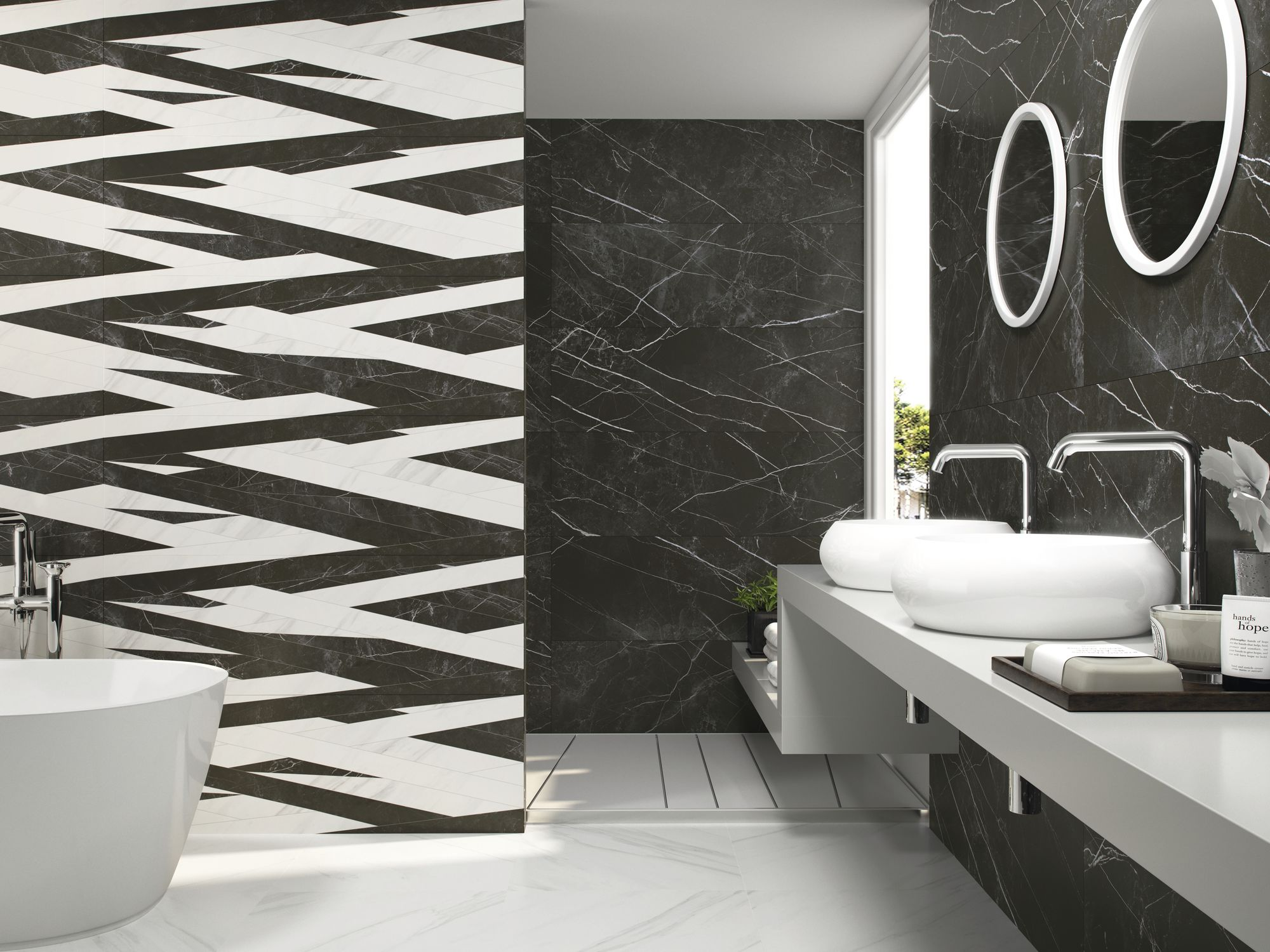 Biało-czarna łazienka z białą wanną wolnostojącą, białą półką wiszącą z dwiema umywalkami nablatowymi, dwoma okrągłymi lustrami oraz płytkami imitującymi marmur