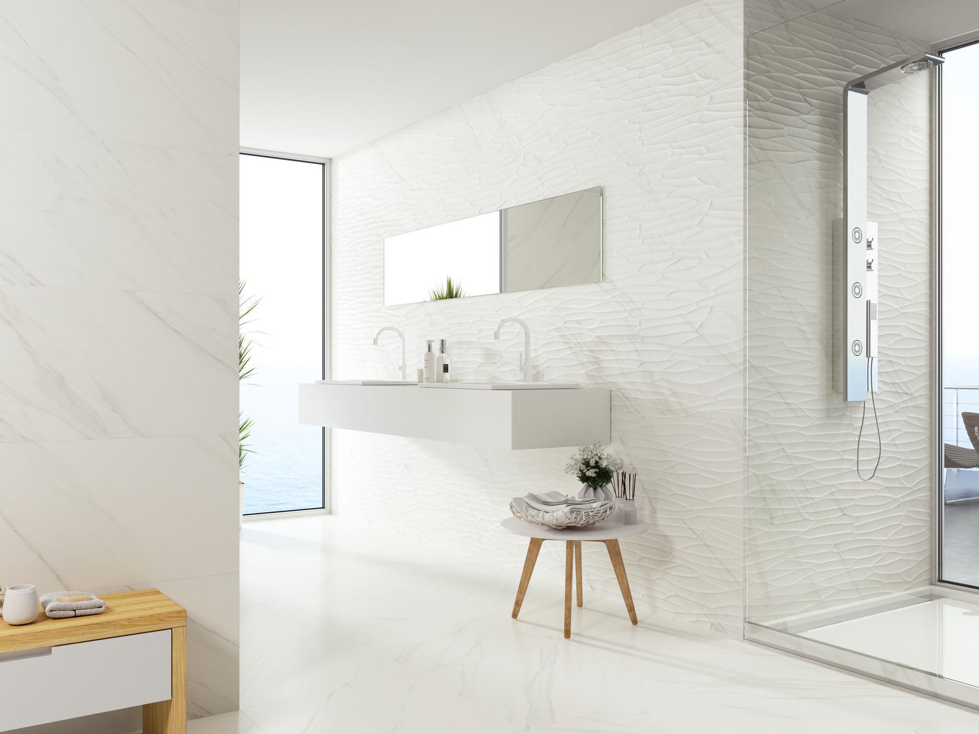 Jasna łazienka z kabiną prysznicową, białą półką wiszącą, dwiema umywalkami i podłużnym lustrem, niskim taboretem oraz płytkami dekoracyjnymi i imitującymi marmur
