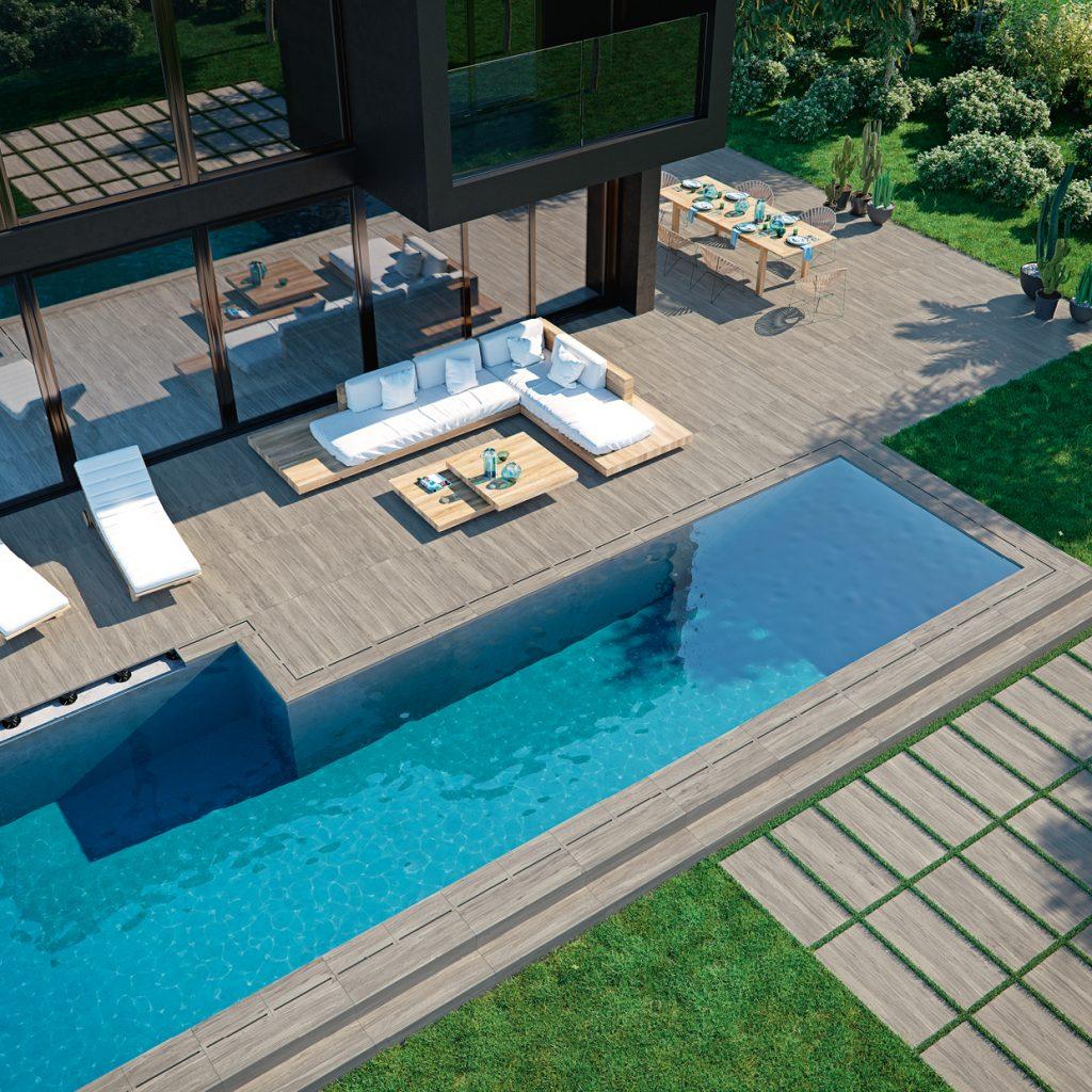 Widok na luksusowy dom z rozległym, drewnianym tarasem z dwoma białym leżakami, białą kanapą, dwoma kwadratowymi stolikami, zastawionym stołem z krzesłami i basenem oraz płytkami drewnopodobnymi