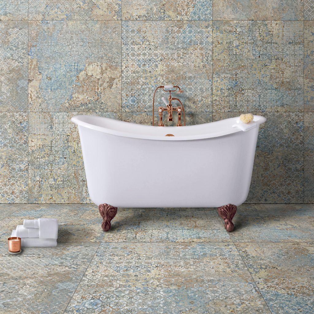 Biała, owalna wanna z ozdobnymi nogami i baterią ścienną w kolorze miedzi antycznej, z białymi ręcznikami i świecą na tle płytek Carpet Vestige Natural