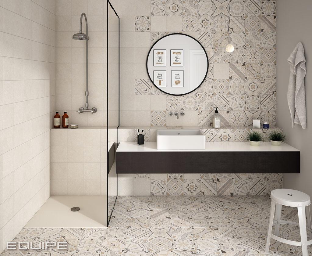 Łazienka utrzymana w beżu z białą umywalką nablatową, okrągłym lustrem, białym stołkiem i kabiną prysznicową oraz płytkami Micro Bone