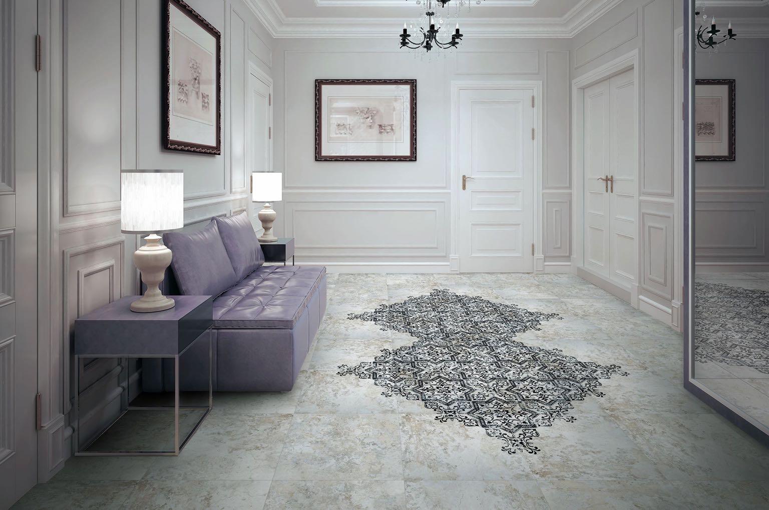 Duży przedpokój z białymi drzwiami i ścianami, obrazami na ścianach, lustrem, fioletową kanapą, dwoma stoliczkami z lampami, żyrandolem i płytkami dekoracyjnymi