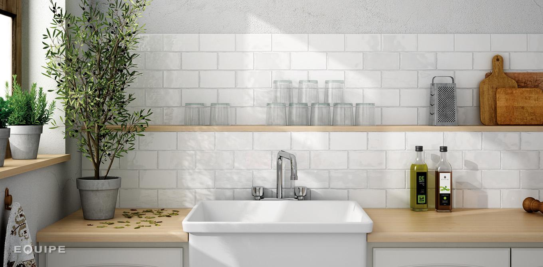 Widok na ścianę w kuchni z białymi kafelkami Masia Blanco, białym zlewem, jasnymi drewnianymi blatami, wiszącą półeczką z naczyniami, kwiatami