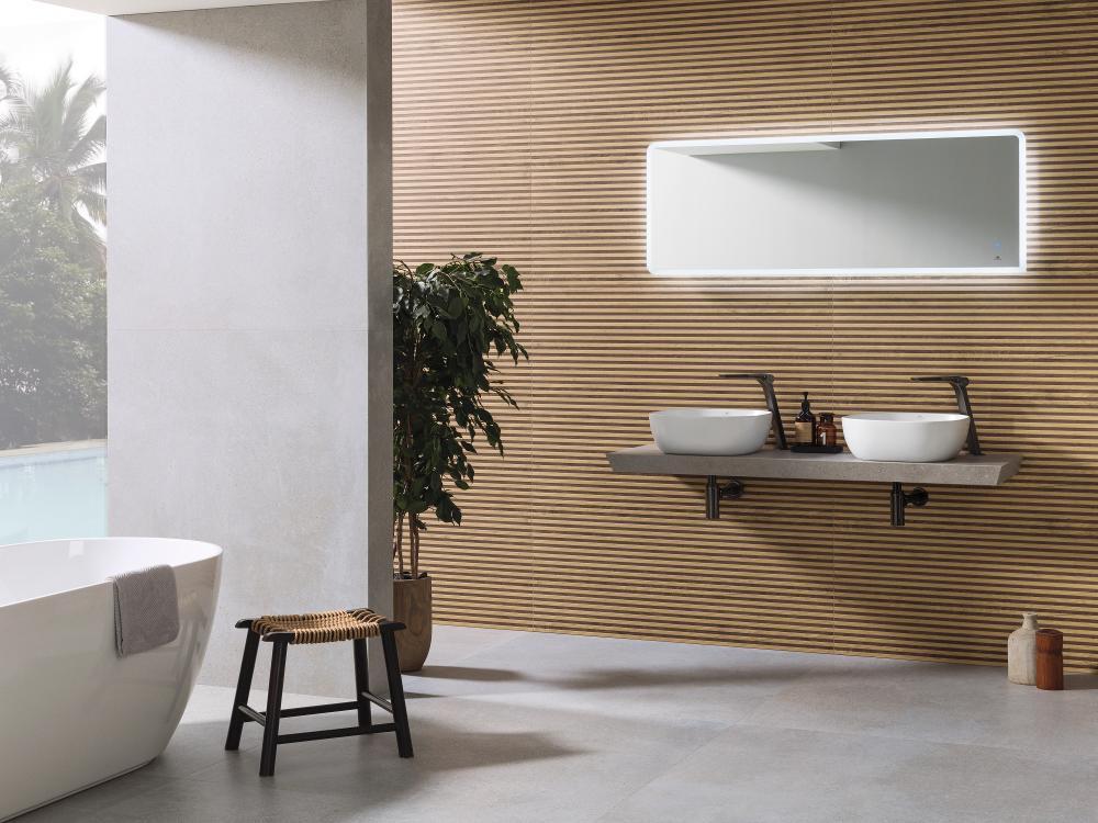 Łazienka ze ścianą wyłożoną płytkami drewnopodobnymi i szarą podłogą z płytkami imitującymi beton, białą wanną wolnostojącą, małym krzesełkiem, wiszącą półką z dwiema umywalkami nablatowymi, prostokątnym lustrem i dużym kwiatem w donicy