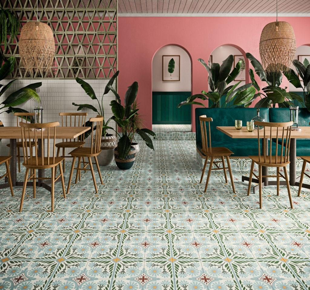 Kolorowa restauracja z różowymi ścianami, zielonymi kanapami, drewnianymi stołami i krzesłami, oryginalnymi wiszącymi lampami, dużą ilością kwiatów doniczkowych i płytkami Altea Olivo Natural