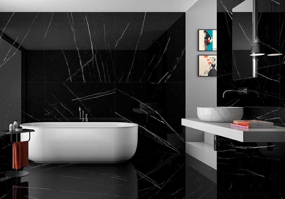Łazienka wyłożona czarnymi płytkami imitującymi marmur z delikatnymi, białymi żyłkami, białą wanną owalną, półką wiszącą z marmurkowym zlewem, prostokątnym lustrem, dwoma obrazkami na ścianie i lampą wiszacą