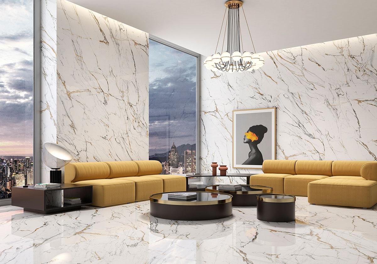 Duży i elegancki salon z żółtymi kanapami, trzema okrągłymi czarnymi stolikami, obrazem na ścianie, żyrandolem, dwoma dużymi oknami i płytkami Oikos Gold