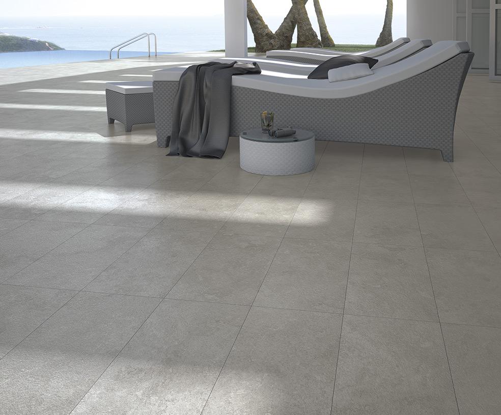 Szary taras łączący się z basenem z trzema leżakami, okrągłym stoliczkiem i widokiem na morze oraz szarymi płytkami podłogowymi imitującymi beton