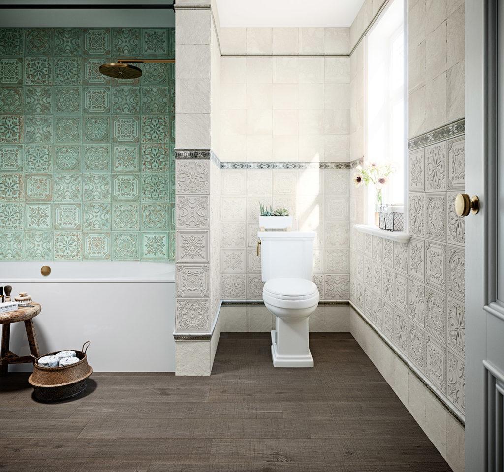 Łazienka z białą toaletą w zagłębieniu, oknem z kwiatkami na parapecie, deszczownicą przymocowaną do ściany, koszykiem i taboretem, płytkami drewnopodobnymi na podłodze i płytkami Gatsby białymi i zielonymi na ścianie