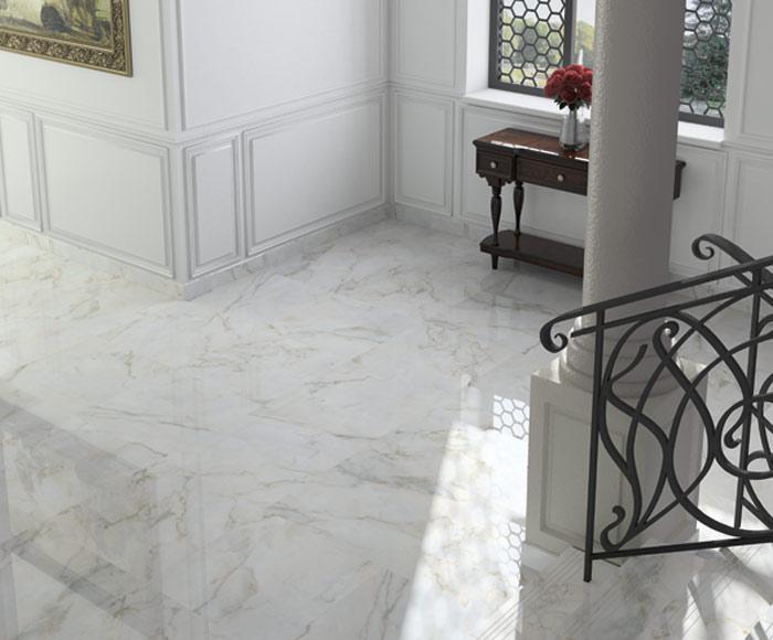 Elegancki przedpokój z jasnymi płytkami imitującymi marmur, brązowym sekretarzykiem i schodami z ozdobną balustradą