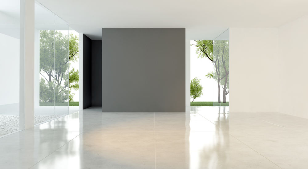 Duży, pusty pokój ze szklanymi drzwiami i oknami z widokiem na ogród, szarą ścianą i jasnymi płytkami w połysku