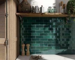 Zbliżenie na ścianę w kuchni wyłożoną zielonymi cegiełkami Artisan Moss Green z jasnym blatem i drewnianą półką wiszącą z naczyniami