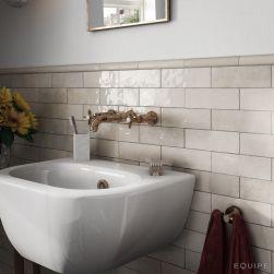 Fragment łazienki z białą umywalką stojącą, baterią podtynkową retro, ręcznikiem, lustrem i płytkami Artisan Ochre