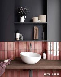 Widok na ścianę łazience do połowy granatową i do połowy wyłożoną różowymi cegiełkami Artisan Rose Mallow z wiszącym drewnianym blatem, białą umywalką nablatową, ręcznikiem, mydłem, lusterkiem i akcesoriami łazienkowymi