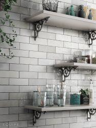 Zbliżenie na ścianę w kuchni wyłożoną białymi cegiełkami Artisan White z trzema białymi półkami wiszącymi z różnymi naczyniami i słoikami