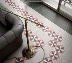 Widok na podłogę wyłożoną płytkami z kolekcji Caprice z ciemną kanapą i drzwiami balkonowymi