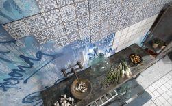 Widok z góry na stary, drewniany stół z miską i jedzeniem oraz na ścianę wyłożoną płytkami patchworkowymi FS Faenza-A 33x33