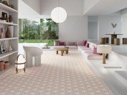 Przestronne pomieszczenie z okrągłą lampą wiszącą, drewnianym okrągłym stołem, białym regałem na książki, różowymi poduszkami do siedzenia oraz płytkami heksagonalnymi Varadero Rose