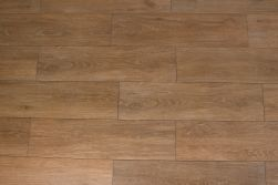 Podłoga stworzona z brązowych płytek gresowych imitujących drewno Viggo Fresno 20x75