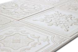 Zbliżenie na wypukły wzór dekoracyjny na białych płytkach z postarzaną powierzchnią Gatsby White Tin 20,1x20,1