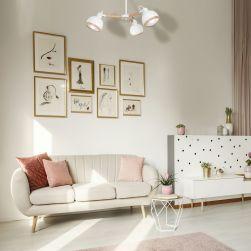 Jasny salon z jasną kanapą, jasnymi stolikami i białym żyrandolem