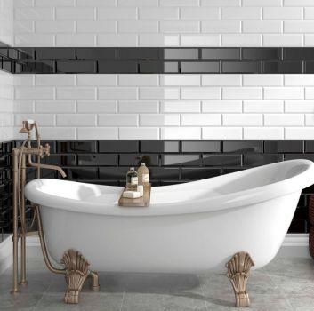 Biało-czarna łazienka z wanną wolnostojącą na mosiężnych nóżkch, brązową pufą oraz wieszakiem