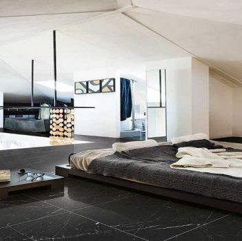 Biała sypialnia z wielkim łóżkiem, szafką nocną oraz dwoma złotymi fotelami
