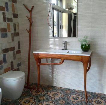 Multikolorowa łazienka z toaletą, drewnianą półką z umywalką oraz prostokątnym lustrem