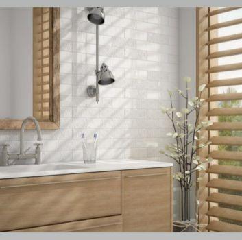 Biała łazienka z drewnianą półką z wbudowaną umywalką, drewnianym lustrem oraz drewnianą roletą w oknie