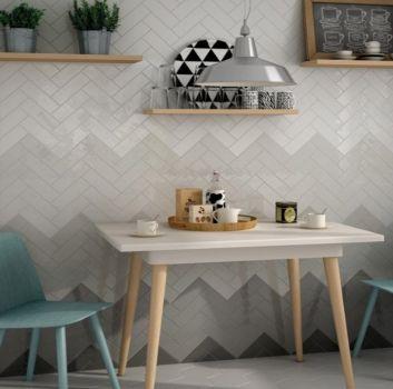 Biało-szara kuchnia z białym stołem na drewnianych nóżkach, niebieskimi krzesłami oraz trzema drewnianymi półkami na dekorację