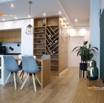 Biała kuchnia z białymi meblami, drewnianym regałem oraz drewnianym blatem z szarymi krzesłami
