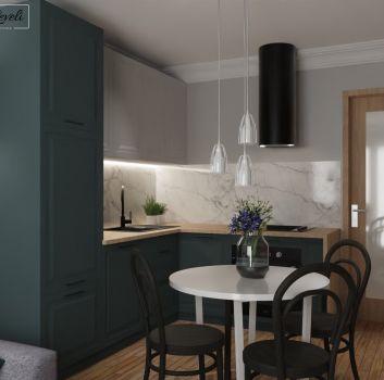 Szaro-biała kuchnia z niebieskimi meblami, białym stolikiem z czarnymi krzesłami oraz salonem