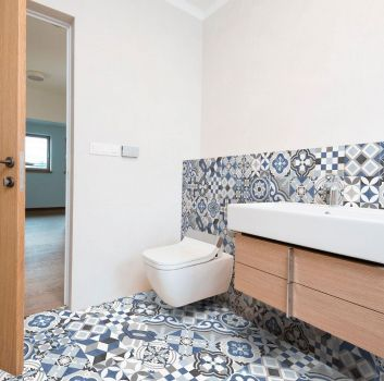 Beżowa łazienka z toaletą, drewnianą półką z umywalką oraz drewnianymi drzwiami do kolejnego pokoju