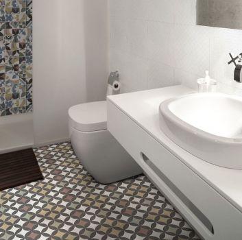 Biała łazienka z prysznicem, toaletą oraz białą półką z umywalką nablatową