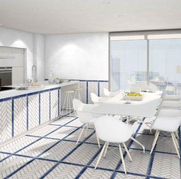 Biało-niebieska kuchnia z białymi meblami, wyspą z dwoma drewnianymi hokerami oraz jadalnią