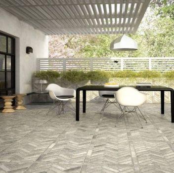 Szary taras z czarnym stołem i białymi krzesłami, drewnianym zadaszeniem oraz dużą ilością roślinności