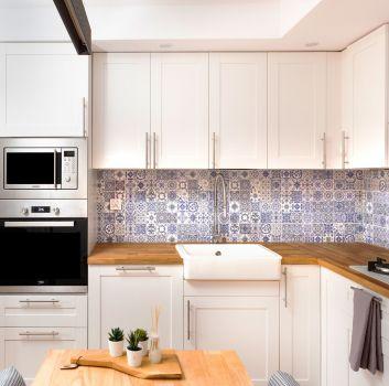 Biało-niebieska kuchnia z białymi meblami, drewnianym stolikiem oraz dwoma szarymi krzesłami