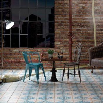 Biało-niebieski salon z dwoma krzesłami, stolikiem oraz skórzanym fotelem