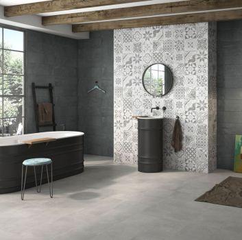 Szaro-grafitowa łazienka z grafitową wanną wolnostojącą, oryginalną ścianą przy której stoi umywalka oraz oryginalną lampą w rogu