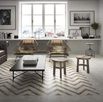 Szary salon ze skórzaną kanapą, dwoma fotelami oraz dwoma drewnianymi taboretami a pośrodku nich jest drewniany stół