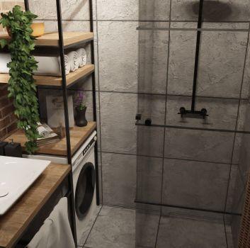 Betonowa łazienka z prysznicem, ceglaną ścianą na której wisi czarne, okrągłe lustro oraz drewnianą szafką z umywalką nablatową