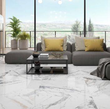 Biały salon z szarą kanapą, szarym stolikiem oraz oknem