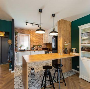 Ceglana kuchnia z białymi meblami, drewnianymi blatami oraz drewnianą wyspą z dwoma, czarnymi hokerami